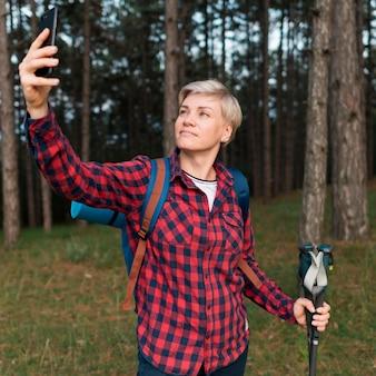 Donna turistica senior che prende selfie nella foresta