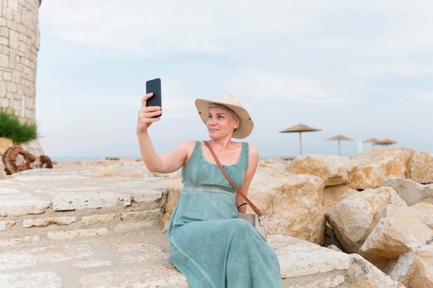Donna turistica senior con il cappello della spiaggia che prende selfie