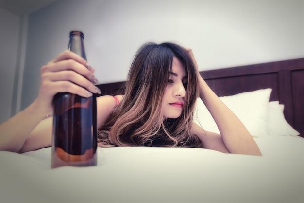 Donna ubriaca sul letto con la bottiglia in mano