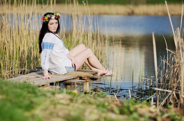 Donna ucraina in camicia che si siede vicino al fiume