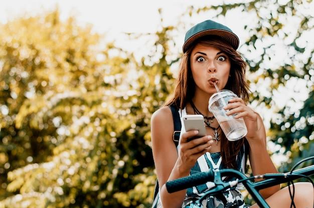 Donna urbana che si siede sulla bici che fa fronte divertente.