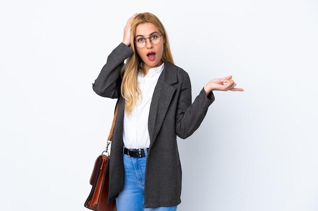 Donna uruguaiana di affari sul muro bianco sorpreso e puntando il dito verso il lato