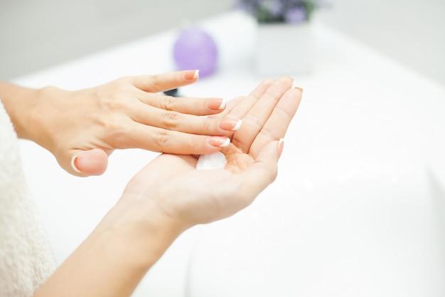 Donna usa prodotti per la cura della pelle a casa