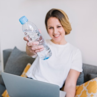 Donna vaga con il computer portatile che mostra bottiglia di acqua