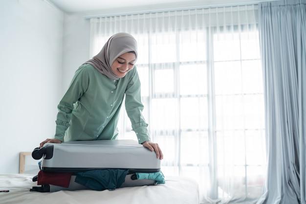 Donna velata che prova a chiudere la sua valigia piena