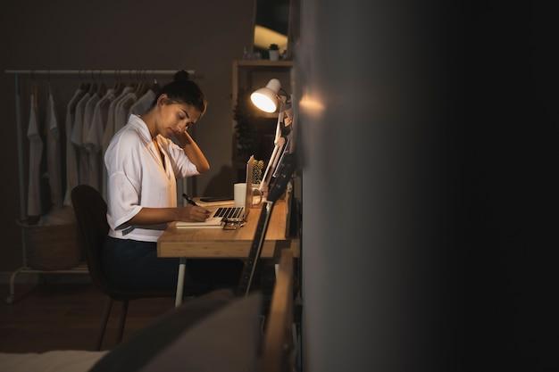 Donna vestita casual seduto sulla scrivania