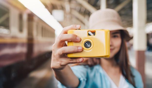Donna viaggia in treno, ragazza con la macchina fotografica di plastica gialla in mano, concetto di stile di vita di viaggio.