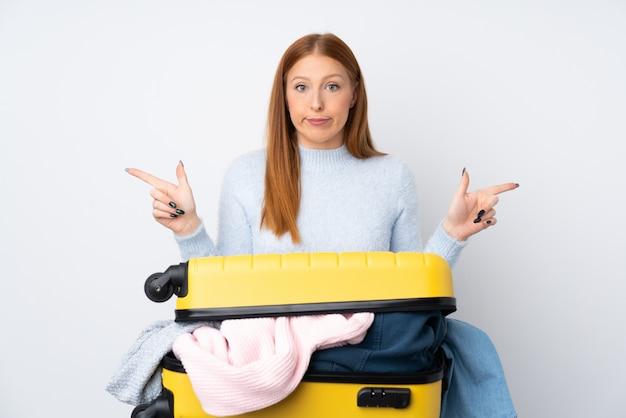 Donna viaggiatore con una valigia piena di vestiti che punta ai lati con dubbi