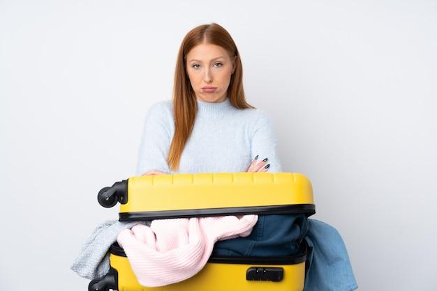 Donna viaggiatore con una valigia piena di vestiti tristi