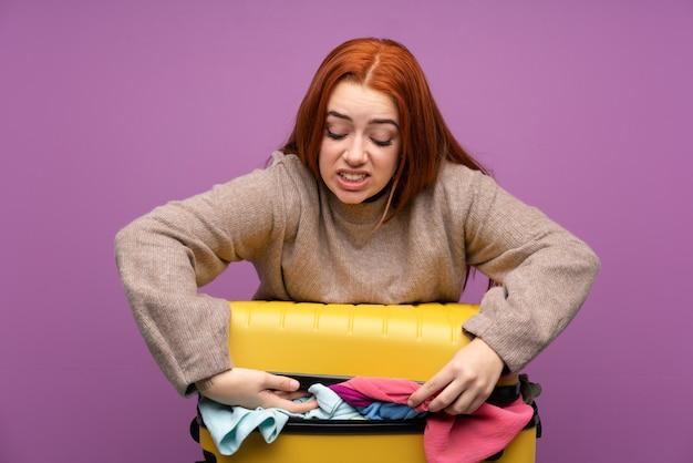 Donna viaggiatore con una valigia piena di vestiti