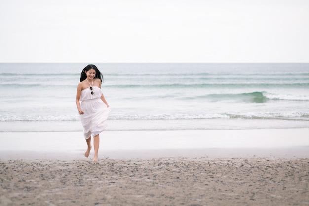 Donna viaggiatore eseguita sulla spiaggia del mare