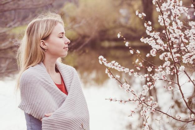 Donna vicino all'albero di albicocca sbocciante