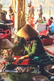 Donna vietnamita che vende alimento su un mercato del bordo della strada in hoi an, provincia di quang nam, vietnam.
