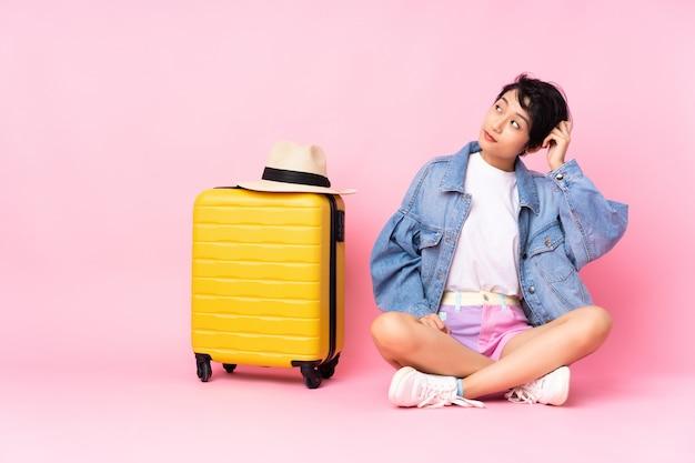 Donna vietnamita del giovane viaggiatore con la valigia che si siede sul pavimento sopra la parete rosa che ha dubbi e con l'espressione confusa del fronte