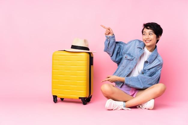 Donna vietnamita del giovane viaggiatore con la valigia che si siede sul pavimento sopra la parete rosa che indica dito il lato
