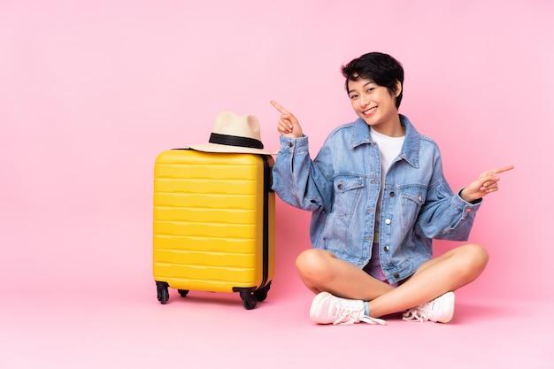 Donna vietnamita del giovane viaggiatore con la valigia che si siede sul pavimento sopra la parete rosa isolata che indica dito ai laterali e felice