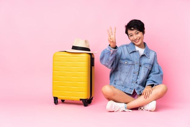 Donna vietnamita del giovane viaggiatore con la valigia che si siede sul pavimento sopra la parete rosa isolata felice e che conta tre con le dita