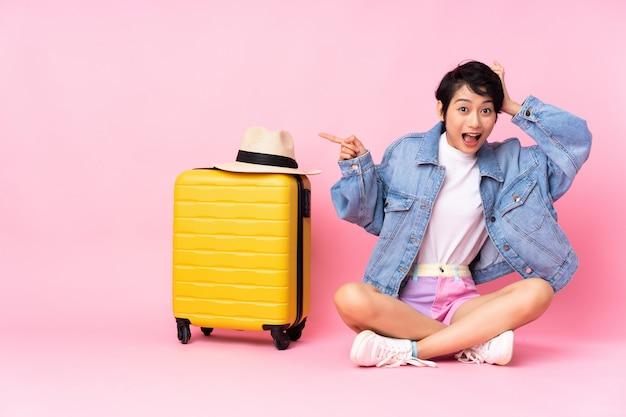 Donna vietnamita del giovane viaggiatore con la valigia che si siede sul pavimento sopra la parete rosa sorpresa e che indica dito al lato