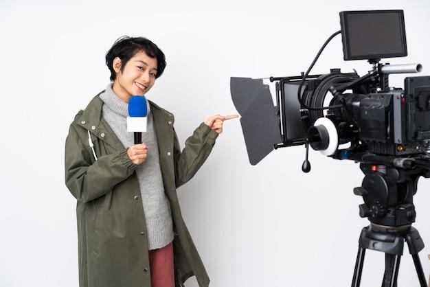 Donna vietnamita del reporter che tiene un microfono e che riferisce le notizie che indicano dito il lato