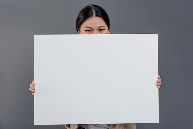 Donna vista frontale con foglio di carta bianco