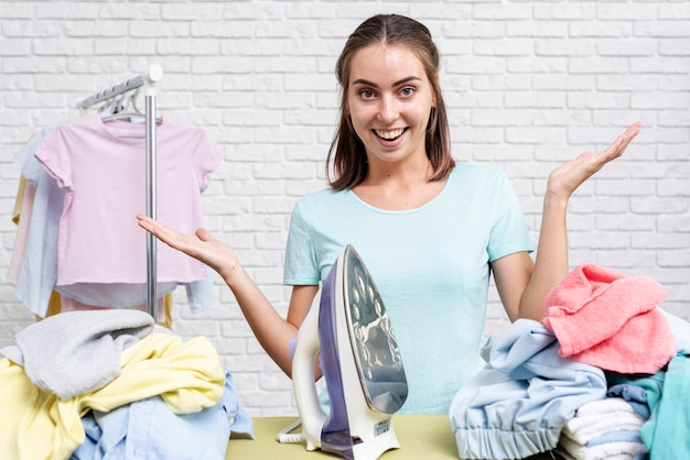 Donna vista frontale pronta per stirare i vestiti