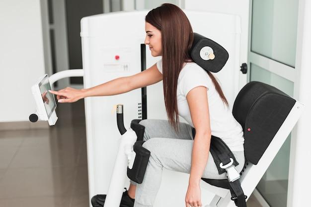 Donna vista laterale utilizzando la macchina medica
