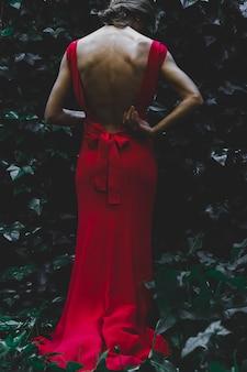 Donna vista posteriore vicino a bush