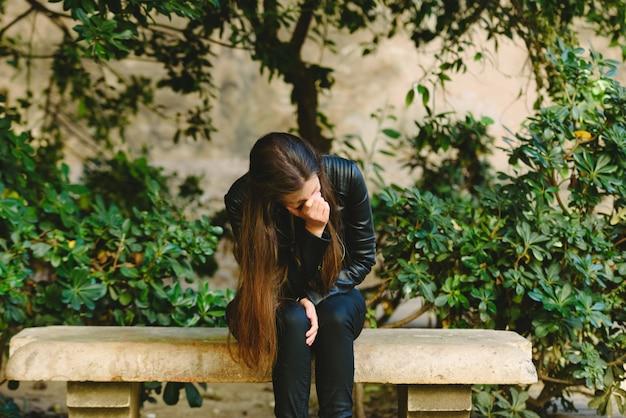 Donna vittima della discussione di una coppia, seduta da sola a pensare di rompere la loro relazione per paura di subire abusi