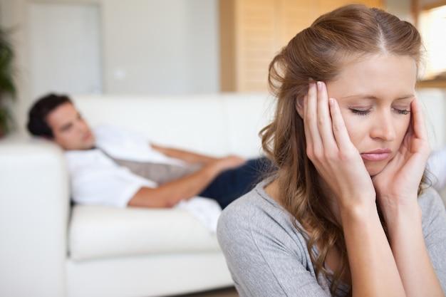 Donna vivendo mal di testa con l'uomo sul divano dietro di lei