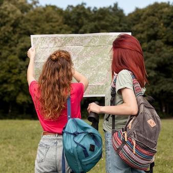 Donne a metà tiro con il binocolo e la mappa in natura