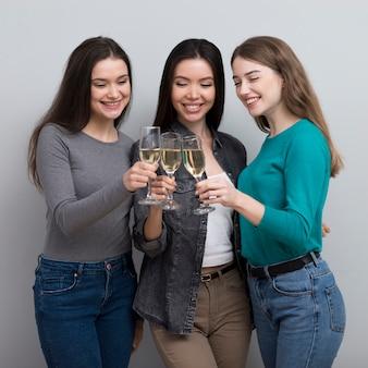 Donne adulte di vista frontale che mangiano champagne insieme