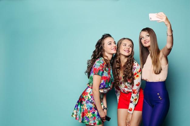 Donne alla moda in abiti luminosi che fanno foto al telefono intelligente.