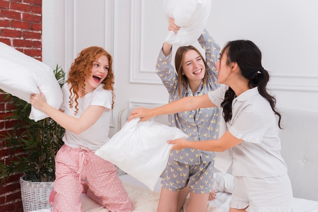 Donne allegre che combattono con i cuscini