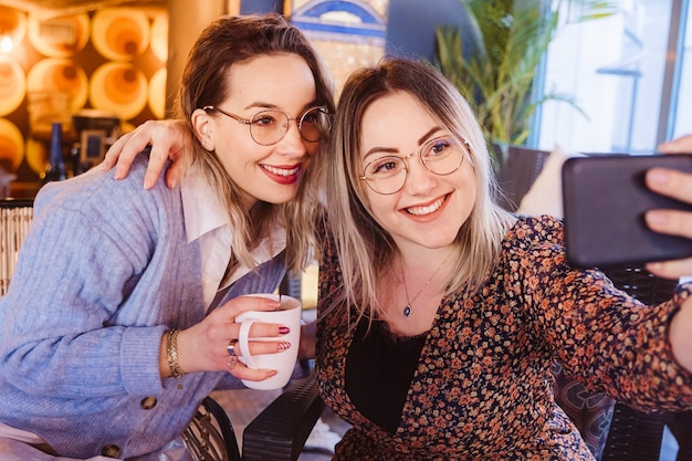 Donne allegre che fanno una videochiamata con un amico con lo smartphone.