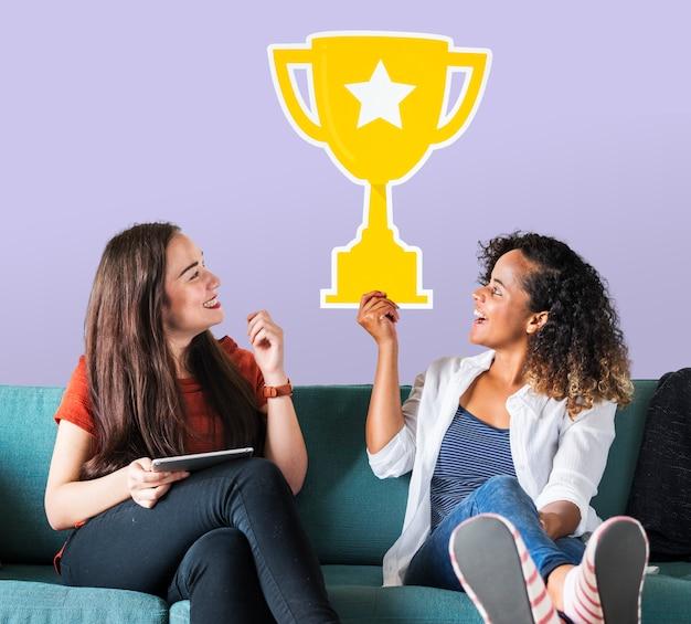 Donne allegre che tengono l'icona del trofeo