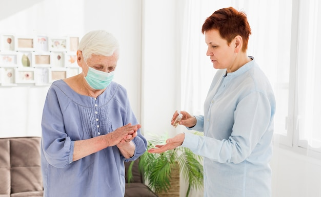Donne anziane che disinfettano le mani mentre a casa