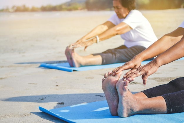 Donne anziane che si esercitano in spiaggia in riva al mare aria fresca, corpo forte
