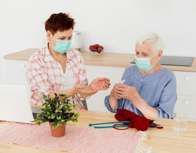 Donne anziane con maschere mediche che si disinfettano le mani mentre lavorano a maglia