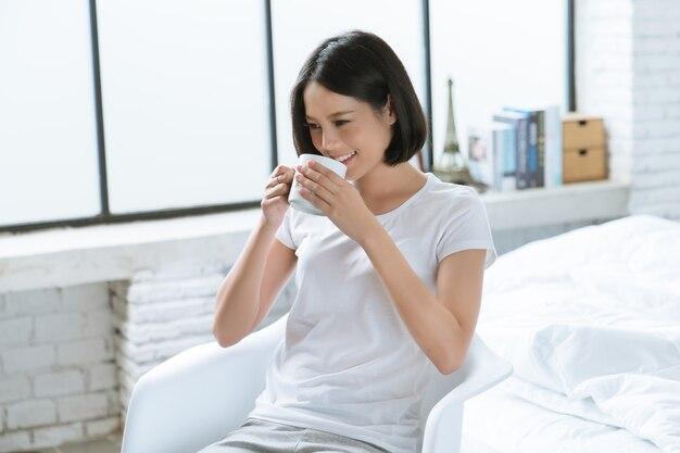 Donne asiatiche bevi caffè dopo il risveglio. nella sua camera da letto