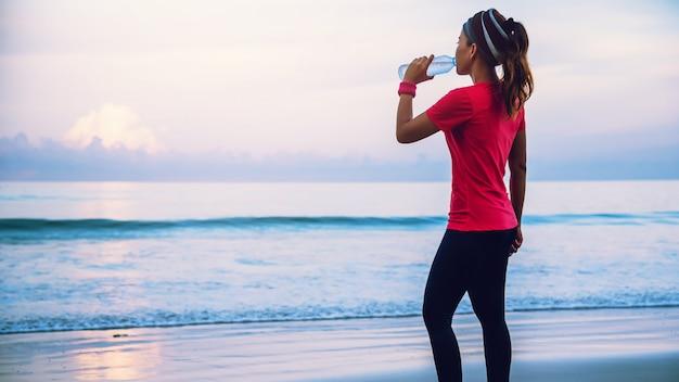 Donne asiatiche che pareggiano allenamento sulla spiaggia di mattina.