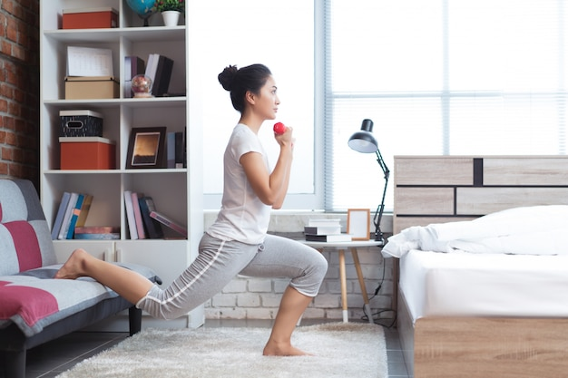 Donne asiatiche che si esercitano a letto la mattina, si sente riposata. fa da squat.