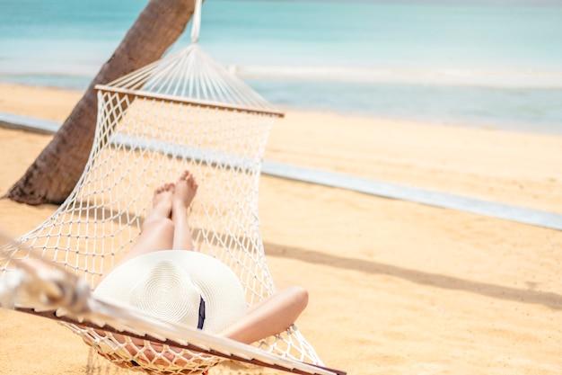Donne asiatiche che si rilassano in vacanza estiva dell'amaca sulla spiaggia