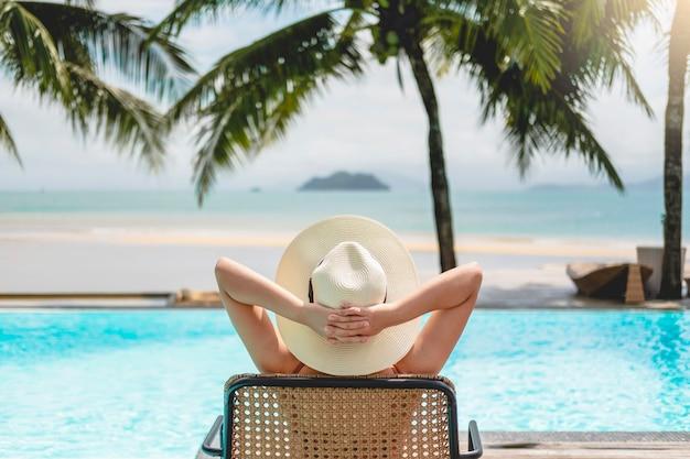 Donne asiatiche che si rilassano nelle vacanze estive della piscina sulla spiaggia