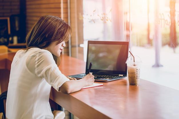 Donne asiatiche che si sono svegliati al caffè con l'azione di progetto di affari di pensiero della nota del computer portatile e di scrittura