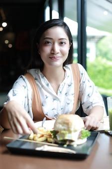 Donne asiatiche che sorridono e felici e godute mangiando gli hamburger al caffè e al ristorante su tempo di rilassamento