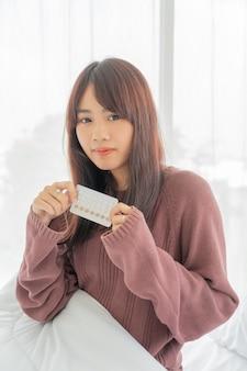 Donne asiatiche che tengono la pillola anticoncezionale