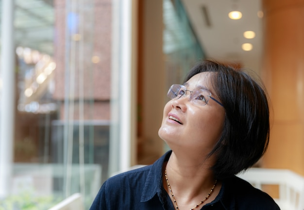 Donne asiatiche con i capelli corti, vestito a maniche corte, occhiali blu seduti vicino al vetro della finestra.