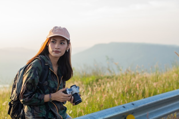 Donne asiatiche con lo zaino che prende una foto sulla vista al picco di montagna della spiaggia di alba