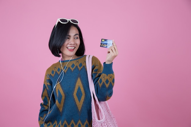 Donne asiatiche con occhiali da sole, borsa rosa e cuffia che mostrano le carte di credito.