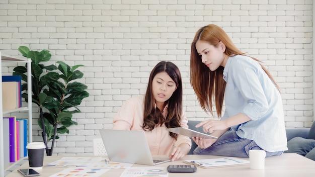 Donne asiatiche creative intelligenti attraenti di affari nell'abbigliamento casual astuto che lavora al computer portatile mentre sedendosi